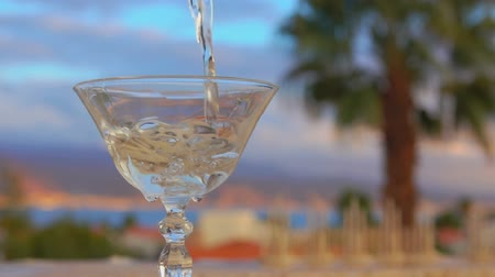 vermouth : Martini is poured into a glass on a background of sea landscape and palm trees