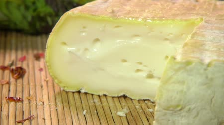 laktóz : Triangular piece of a french soft creamy brie cheese is taken out from a whole cheese Stock mozgókép