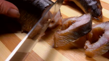 paling : Close up of a female hands cutting smoked eel into portions with a knife on a wooden board Stockvideo