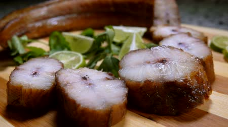paling : Smoked eel pieces with lime slices are lying on a wooden bamboo board