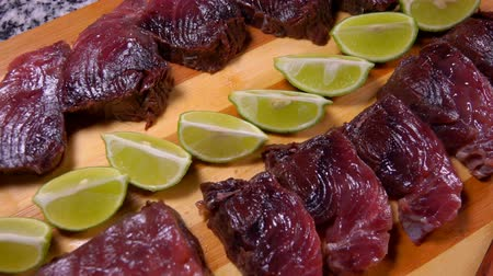塩漬けの : Top view of lightly salted tuna and lime on a bamboo cutting board. Panoramic camera movement. 動画素材