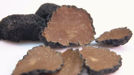 hlíza : Close up of a rare black truffle fungus cutted into pieces on a white surface. Panoramic view of a texture of a black truffle Dostupné videozáznamy