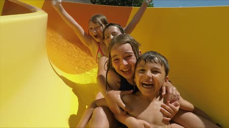 waterslide : Happy children are riding down a slide in an aquapark. Children laugh merrily and wave their hands