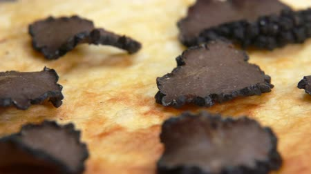 yermantarı : Close up of a french omelette sprinkled with slices of a black truffle mushroom Stok Video