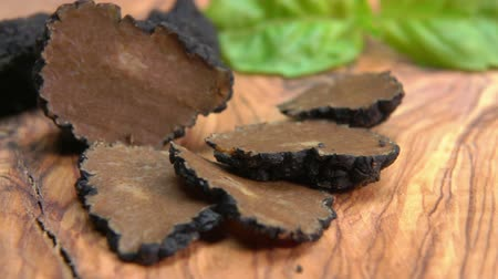 cuisine dark : Close up of a rare black truffle fungus cutted into pieces on a wooden board. Panoramic view of a texture of a black truffle Stock Footage