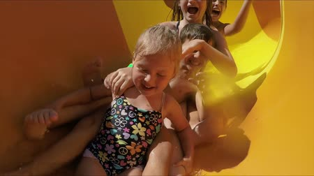 waterslide : Group of happy children riding down an orange slide in a water park. Children laugh merrily and wave their hands