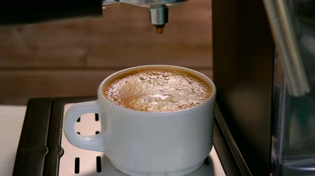 titular : Coffee drops from the coffee machine into a white cup with capuccino