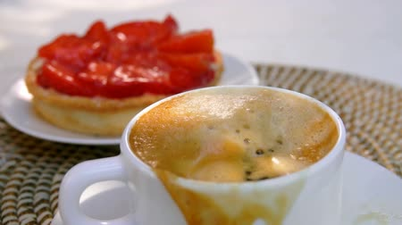tartó : Sugar cube falls into espresso coffee in a white cup on the background of french pastry