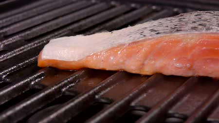 truta : Close up of a raw salmon fillet fryed on the metall grill with fire