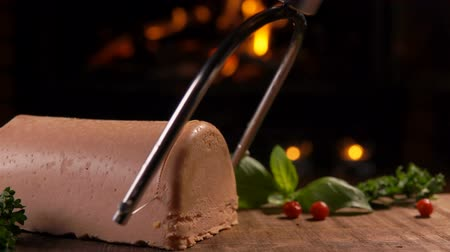quebradiço : Special string knife cuts foie gras into slices on a wooden board on the background of a burning fireplace