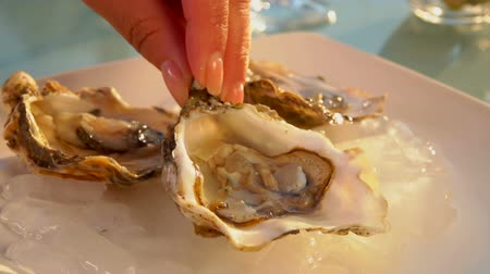 oysters : Female hand lay an open oyster on a white plate with melted ice