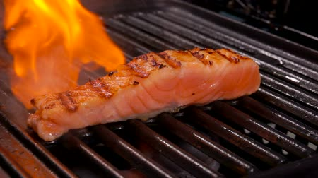 truta : Piece of raw salmon fillet fryed on the metall grill with fire