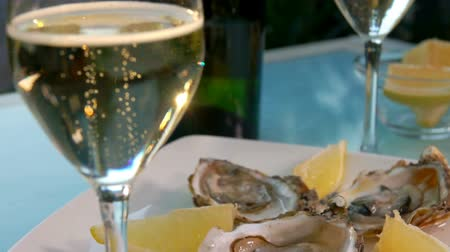 oysters : Panorama from a glass with champagne to the open oysters on a white plate with ice and lemon