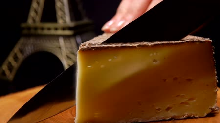 moldy : Knife cuts a piece of french hard goat cheese wooden boards against the background of the Eiffel Tower model. Stock Footage