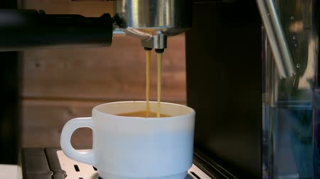kafeterya : Espresso coffee is poured into a white cup from the black coffee machine