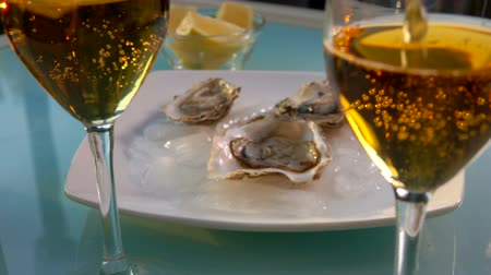 oysters : Panorama from a glass with champagne to the open oysters on a white plate with ice