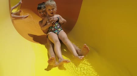 waterslide : Group of happy smiling children riding down an orange slide in a water park. Children laugh merrily and wave their hands Stock Footage