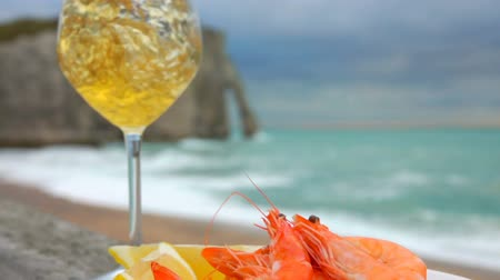 shellfish dishes : Wine is poured in glass against plate with delicious shrimps and lemon on the background of the ocean coast on a cloudy day in Etretat, France