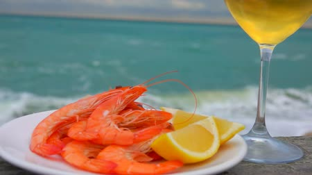 shellfish dishes : Delicious shrimps with lemon and white wine on the background of the ocean coast on a cloudy day in Etretat, France Stock Footage