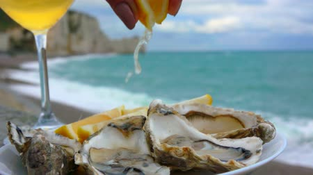 osztriga : Lemon squeezed onto fresh oysters on the background of the ocean coast on a cloudy day in Etretat, France