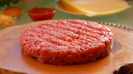 preparado : Cesam bun falls on the table. Prepared products for hamburgers on the table