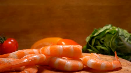 shellfish dishes : Peeled shrimps fall on a wooden board on the background of tomato and lettuce Stock Footage