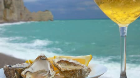 oysters : Panorama from the white wine poured in a glass to the plate full of fresh oysters against the ocean on a cloudy day in Etretat, France