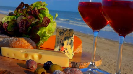 bílé víno : Romantic and delicious picnic by the sea with red wine, cheese, bread, lettuce and olives