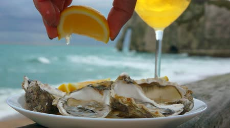 oysters : Hand is squeezing a fresh lemon juice onto the plate full of fresh oysters. Glass of white wine against the ocean on a cloudy day in Etretat, France