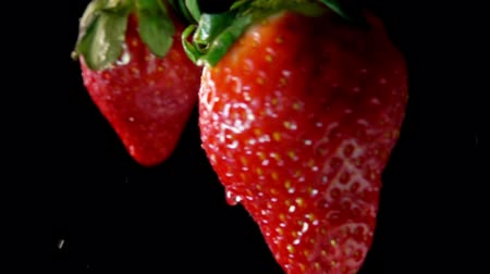 bűbájos : Two juicy tasty large red strawberries collide each other with splashes of water on a black background