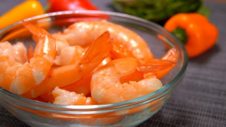 rákfélék : Hand lay a peeled shrimp in a glass bowl on the background of tomato and lettuce