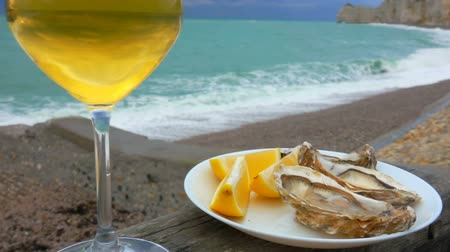 oysters : Plate full of fresh oysters and lemons with a glass of white wine against the ocean on a cloudy day in Etretat, France