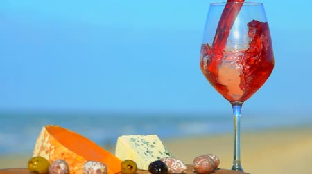 Бордо : Red wine is poured in a glass next to the cheese board. Romantic picnic by the sea with red wine, cheese, bread, lettuce and olives