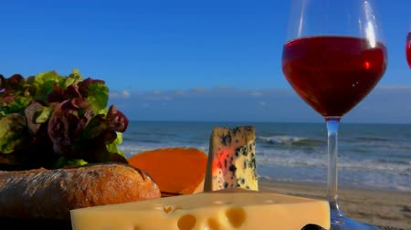 rokfor : Romantic picnic on the sea shore with red wine, cheese, bread, lettuce and olives