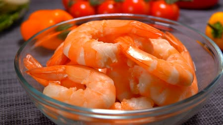 oysters : Hand lay peeled shrimps in a glass bowl on the background of tomato and lettuce
