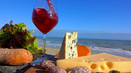 Бордо : Red wine is poured in a glass next to the cheese plate. Romantic picnic by the sea with red wine, cheese, bread, lettuce and olives Стоковые видеозаписи