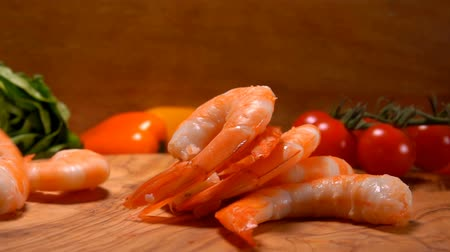 oysters : Delicious Peeled shrimps fall on a wooden board on the background of tomato and lettuce Stock Footage