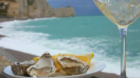 oysters : White wine poured in a glass next to the plate full of fresh oysters against the ocean on a cloudy day in Etretat, France
