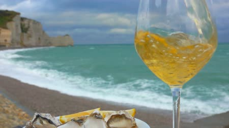 naživu : Close up of a white wine poured in a glass next to the plate full of fresh oysters against the ocean on a cloudy day in Etretat, France
