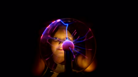 geheimnisvoll : Beautiful black-eyed girl touches the Tesla lamp with her hands. She looks at Teslas lamp. Videos
