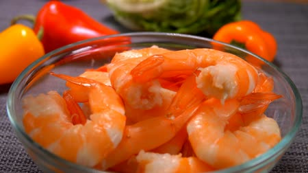 shellfish dishes : Hand lay a delicious peeled shrimp in a glass bowl on the background of tomato and pepper