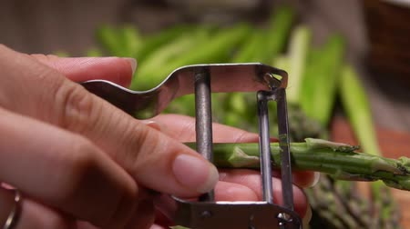 espargos : Hand is peeling green asparagus with a special knife on the background of an asparagus spears