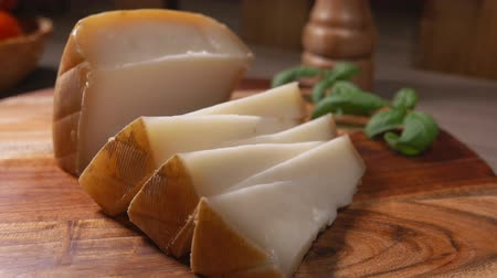 laktóz : Semi hard sheep cheese cut in a triangular pieces laying on the wooden board with basil