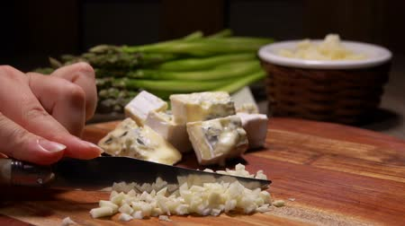 espargos : Hand is choping a garlic with a knife on the background of green asparagus spears Stock Footage