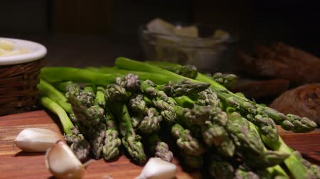 espargos : Peeled green asparagus spear falls onto a wooden board next to tha garlic and cheese