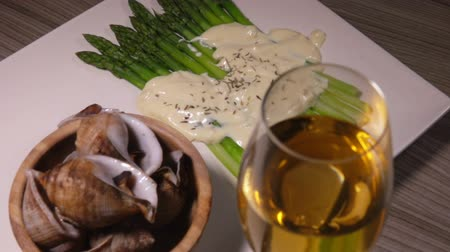ракушки : Cooked sea escargo snails with a side dish of green asparagus under the cheese sauce and white wine in a glass Стоковые видеозаписи