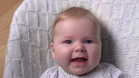 nurses : Little adorable blue-eyed one month baby on a white blanket is looking at the camera