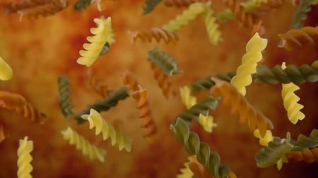 olive colored : Colored pasta fusili fly up on a yellow ochre background in slow motion