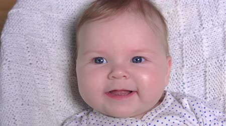 baby chubby : Close up of an adorable blue-eyed baby laying on a white blanket and smiling happily
