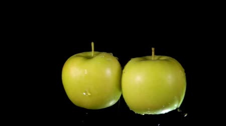 bounce : Two wet ripe green apples collide with each other and scatter in different directions. Extreme close-up slow motion